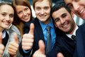 Excellent portrait of five business partners keeping thumbs up and looking at camera with smiles Stock Photos