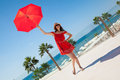Excellent recreation happy young woman in a red dress with a red umbrella on seafront background Royalty Free Stock Photography