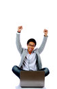 Excited Asian man using laptop on the floor Royalty Free Stock Photo