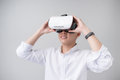 Excited asian man in a VR goggles and gesturing with his hands Royalty Free Stock Photo
