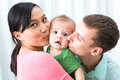 Excited baby image of a young cheerful family kissing his little on the foreground Stock Photography