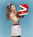 Excited birthday girl opening surprise gift surprised smiling beautiful young woman holding an open box and looking at the present Royalty Free Stock Image