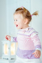 Excited blond little girl with ponytail jumping on bed laughing and screaming white interior bedroom night lamp Stock Photos