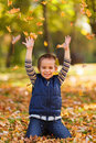 Excited boy playing little with leaves in the park Stock Photos