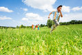 Excited boy runs away from his mates in field during summer time Royalty Free Stock Image