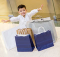 Excited boy shopping bags looking very happy Royalty Free Stock Image