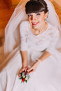 Excited bride in gorgeous white dress waiting for her wedding posing with cute floral boutonniere Royalty Free Stock Photo