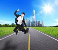 Excited business man jump and run on the road with city background concept for success asian Stock Photography