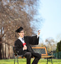 Excited college graduate taking a selfie in park on bench shot with tilt and shift lens Royalty Free Stock Image