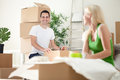 Excited couple in new home unpacking boxes concept moving into a Stock Photos