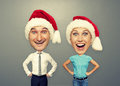 Excited couple in santa hat over grey background Stock Photo