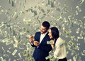 Excited couple under dollar s rain happy with money standing Royalty Free Stock Images