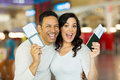 Excited couple vacation going on a and holding passport boarding pass at airport Royalty Free Stock Photo