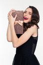 Excited elated pretty woman with retro hairstyle hugging gift box young in black dress over white background Royalty Free Stock Photography