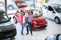 Excited family buying a new car in the dealership saloon Royalty Free Stock Photos