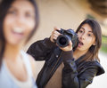 Excited female mixed race photographer spots celebrity and ready outside Stock Photos