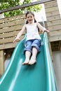 Excited girl playing on slide in park full length of young Royalty Free Stock Images