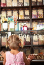 Excited Girl Standing In Sweet Shop Royalty Free Stock Images