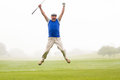 Excited golfer jumping up and smiling at camera Royalty Free Stock Photo