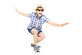 Excited guy with cap and sunglasses skating on a skate board isolated white background Royalty Free Stock Images