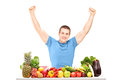 Excited guy gesturing happiness seated on a table full of fruits Royalty Free Stock Image