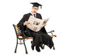 Excited guy in graduation gown reading a newspaper seated on ben bench isolated white background Stock Photo