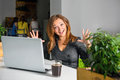 Excited happy businesswoman with raised arms sitting at the table with laptop celebrating her success funny image of winner or su Stock Photo