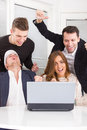 Excited happy group of friends winning online using laptop smiling Stock Photography