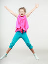 Excited happy little girl kid jumping for joy in air joyful cheerful in studio with arms raised up Stock Photos
