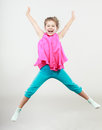 Excited happy little girl kid jumping for joy in air joyful cheerful in studio with arms raised up Royalty Free Stock Photography