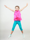 Excited happy little girl kid jumping for joy in air joyful cheerful in studio with arms raised up Royalty Free Stock Photo