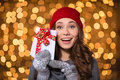 Excited happy young woman holding blank cards with red ribbon in hat and knitted mittens over shining background Royalty Free Stock Photo