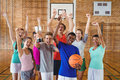 Excited high school kids holding trophy in basketball court Royalty Free Stock Photo