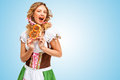 Excited and hungry young oktoberfest woman wearing a traditional bavarian dress dirndl holding a pretzel in hands on blue Stock Photos