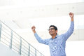 Excited indian business man successful asian businessman with arms up celebrating his victory modern office building as background Stock Photography