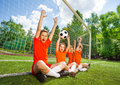 Excited kids sit in row with football and arms up on field grass near woodwork the air Royalty Free Stock Photography