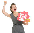 Excited landlord with home for sale sold sign Stock Photo