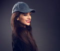 Excited laughing beautiful brunette woman in baseball blue cap w