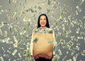 Excited laughing woman holding money businesswoman standing under dollar s rain and big paper bag with Stock Photos