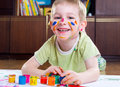 Excited little boy painting with colorful paints Stock Photography