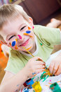 Excited little boy painting with colorful paints Royalty Free Stock Photography