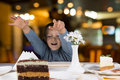 Excited little boy reaching for a slice of cake large layered chocolate cream with look eager anticipation as he sits at Stock Photos