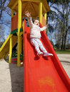 Excited little girl sliding down a slide vertical shot of an baby at playground outdoors Royalty Free Stock Image