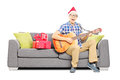 Excited male with christmas hat sitting on a sofa and playing a young modern an acoustic guitar isolated white background Royalty Free Stock Photo