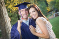 Excited male graduate in cap and gown and girl happy pretty celebrate outside Stock Images