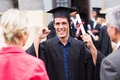 Excited male graduate holding his diploma at graduation Royalty Free Stock Photography