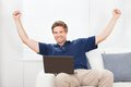 Excited man with laptop raising hands Royalty Free Stock Photo