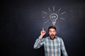 Excited man pointing up over blackboard background with light bulb Royalty Free Stock Photo