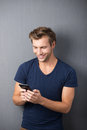 Excited man reading an sms on his mobile handsome young message phone with a beaming smile Royalty Free Stock Photography