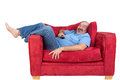 Excited man watching television laughing as he lies back barefoot on a comfortable red sofa with the remote control in his hand Royalty Free Stock Images